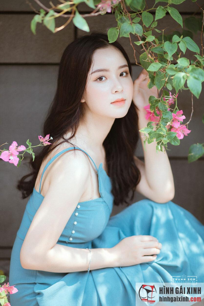 Thiếu nữ dễ thương e ấp thẹn thùng bên dàn hoa giấy